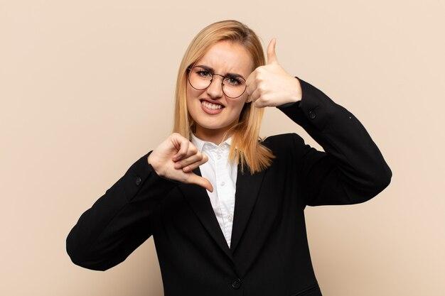 Jonge blonde vrouw die zich verward, onwetend en onzeker voelt en het goede en slechte in verschillende opties of keuzes weegt