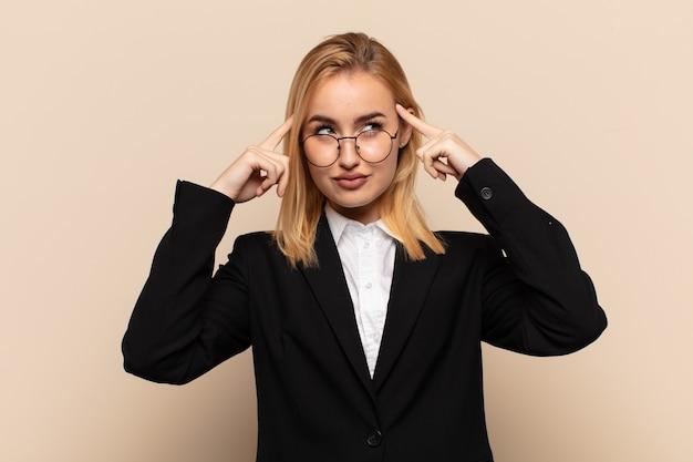 Jonge blonde vrouw die zich verward voelt of twijfelt, zich concentreert op een idee, hard nadenkt, op zoek is naar ruimte aan de zijkant