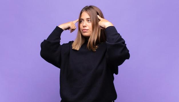 Jonge blonde vrouw die zich verward voelt of twijfelt, zich op een idee concentreert, hard nadenkt, ruimte aan de zijkant wil kopiëren