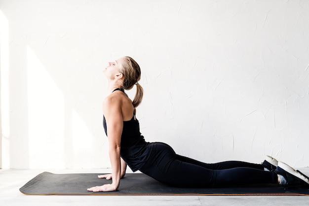 Jonge blonde vrouw doet yoga of thuis uitrekken