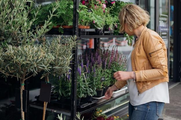 Jonge blonde vrouw, eigenaar van bloemenwinkel, corrigeert de planten die op het straatraam worden weergegeven. kleine onderneming. handel in bloemen. bloemsierkunst en tuinieren. levensstijl. bloemenwinkel.