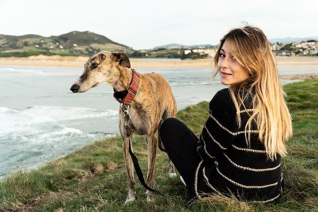 Jonge blonde vrouw en haar windhond glimlachen en genieten van hij uitzicht op de rivier naar de zee in noord-spanje