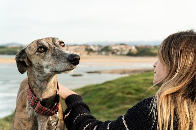 Jonge blonde vrouw en haar windhond op de kust