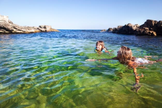 Jonge blonde vrouw en klein blij meisje zwemmen en plezier maken in helder zeewater met rotsen op de achtergrond op heldere zomerdag