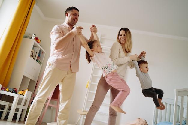 Jonge blonde vrouw en man die kinderen met de handen optillen en met ze zwaaien en gelukkige familie