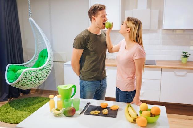 Jonge blonde vrouw geeft haar man een biologische appel tijdens het koken in de keuken.
