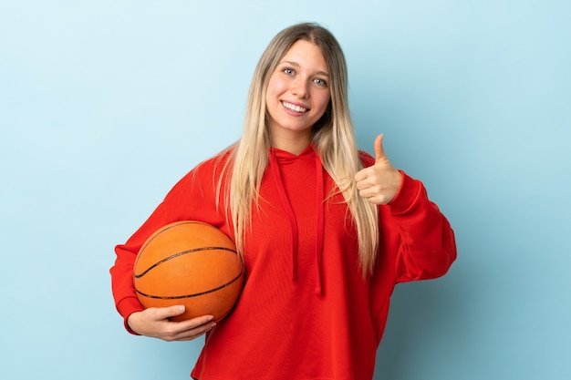 Jonge blonde vrouw geïsoleerd op blauwe muur basketbal spelen en met duim omhoog