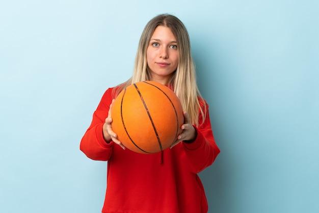 Jonge blonde vrouw geïsoleerd op blauwe muur basketbal spelen