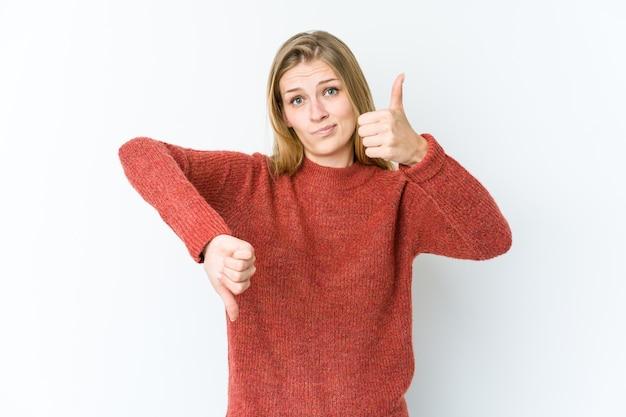 Jonge blonde vrouw geïsoleerd op een witte muur met duimen omhoog en duimen naar beneden