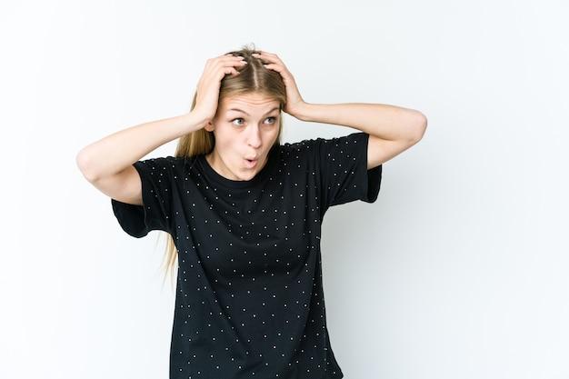 Jonge blonde vrouw geïsoleerd op een witte muur schreeuwen, erg opgewonden, hartstochtelijk, tevreden met iets