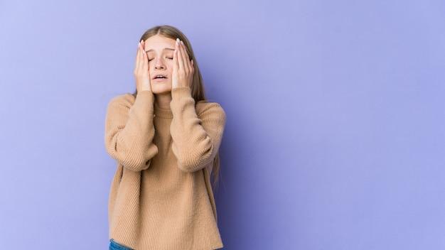 Jonge blonde vrouw geïsoleerd op paarse achtergrond troosteloos janken en huilen.