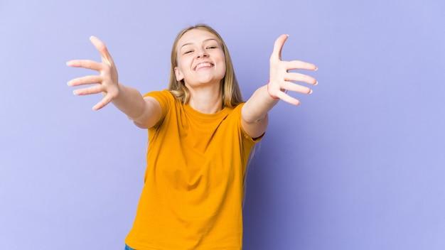 Jonge blonde vrouw geïsoleerd op paarse muur voelt zich zelfverzekerd en geeft de camera een knuffel