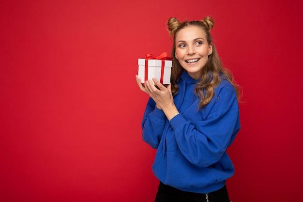 Jonge blonde vrouw geïsoleerd op rode achtergrond muur dragen blauwe trendy hoodie bedrijf geschenkdoos en op zoek naar de zijkant. kopieer ruimte, mockup
