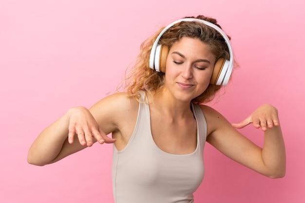 Jonge blonde vrouw geïsoleerd op roze achtergrond muziek luisteren en dansen
