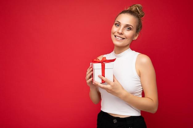 Jonge blonde vrouw geïsoleerd over kleurrijke muur als achtergrond