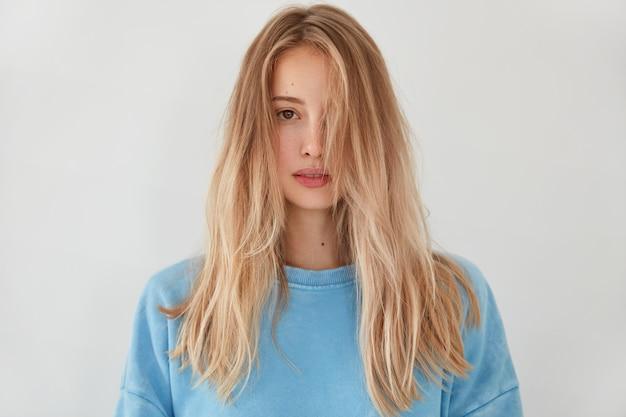Jonge blonde vrouw, gekleed in blauwe trui