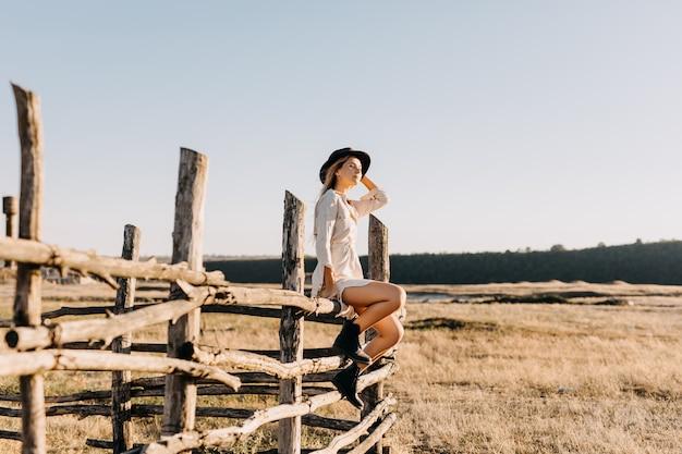 Jonge blonde vrouw, gekleed in leren laarzen en een hoed, zittend op een houten hek op een boerderij