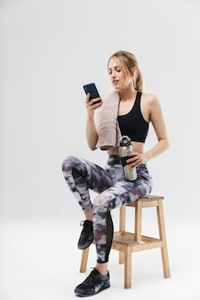 Jonge blonde vrouw gekleed in sportkleding die smartphone gebruikt terwijl ze op een stoel zit na een training in de sportschool geïsoleerd over een witte muur