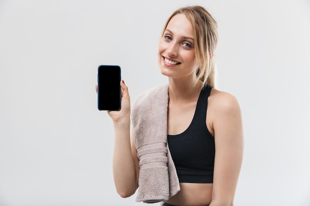 Jonge blonde vrouw gekleed in sportkleding met handdoek over nek met smartphone tijdens training in sportschool geïsoleerd over witte muur