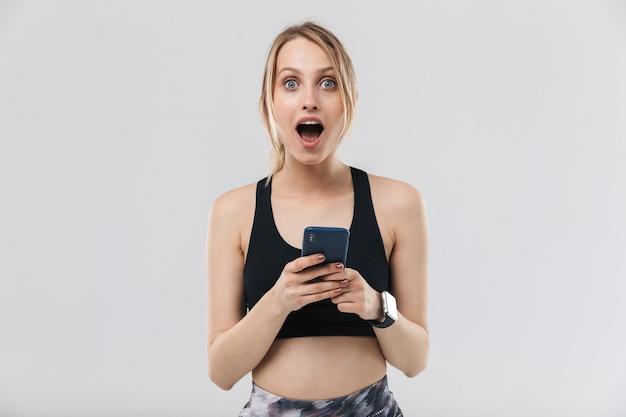 Jonge blonde vrouw gekleed in sportkleding met smartphone tijdens training in sportschool geïsoleerd over witte muur