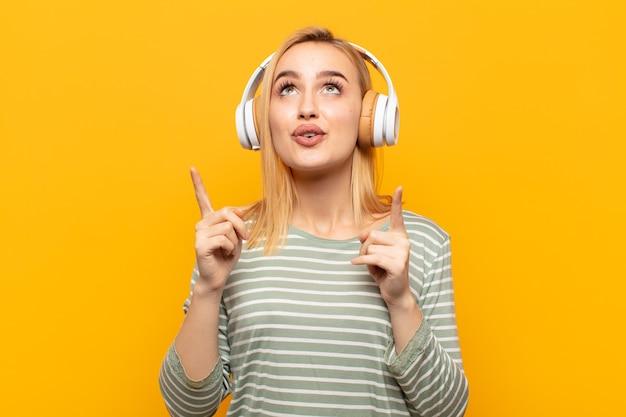 Jonge blonde vrouw gevoel onder de indruk en met open mond naar boven gericht met een geschokte en verbaasde blik