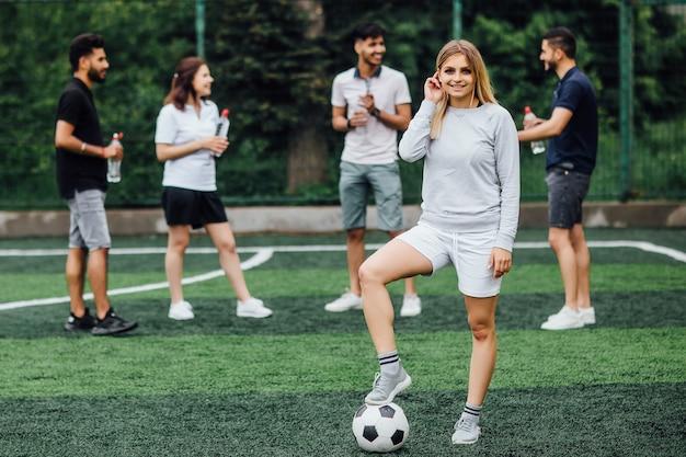 Jonge, blonde vrouw glimlachend en gelukkig, met voetbal, opgewonden om een spelletje te spelen