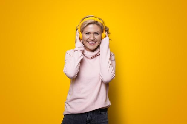 Jonge blonde vrouw glimlachend in de camera tijdens het luisteren naar muziek met een koptelefoon op een gele muur