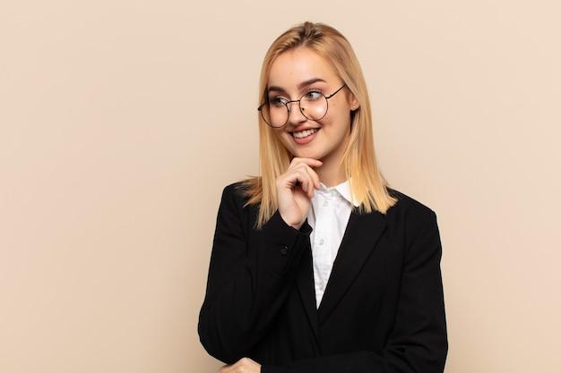 Jonge blonde vrouw glimlachend met een gelukkige, zelfverzekerde uitdrukking met de hand op de kin, zich afvragend en opzij kijkend