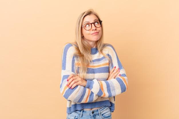 Jonge blonde vrouw haalt haar schouders op, voelt zich verward en onzeker