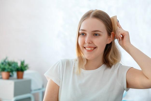 Jonge blonde vrouw haar verwarde haren kammen met houten kam haarborstel. ochtendroutine in de badkamer