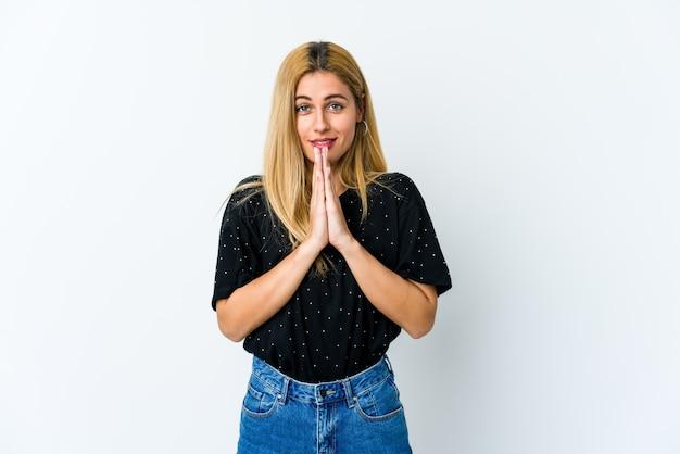 Jonge blonde vrouw hand in hand bidden in de buurt van mond, voelt zich zelfverzekerd.