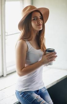 Jonge blonde vrouw in beige hoed met een kopje koffie