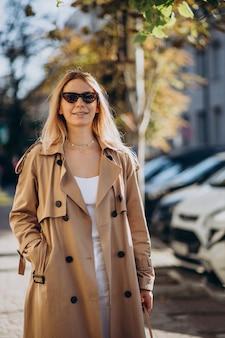 Jonge blonde vrouw in beige jas die op straat loopt