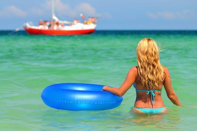 Jonge blonde vrouw in blauwe bikini achteruit in stil zeewater staan met zwemmen cirkel en schip horizon kijken op zonnige zomerdag. geluk, vakanties en vrijheid concept