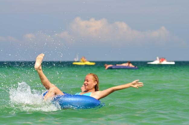 Jonge blonde vrouw in blauwe bikini rijden op cirkel zwemmen in zee en glimlachend op zonnige zomerdag. geluk, vakanties en vrijheid concept
