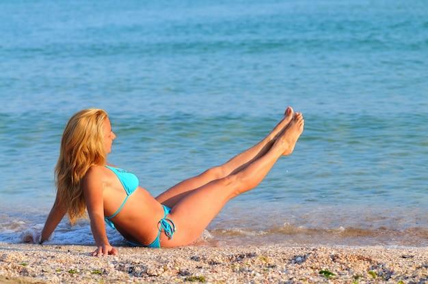 Jonge blonde vrouw in blauwe bikini zittend op de rand van de zee met haar benen omhoog en ontspannen op zonnige zomerdag. geluk, vakanties en vrijheid concept