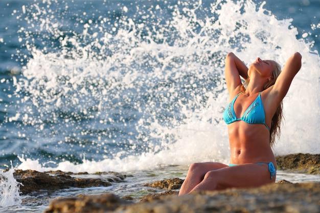Jonge blonde vrouw in blauwe bikini zittend op de rotsen en genieten van druppels golven op heldere zonnige zomerdag. geluk, vakanties en vrijheid concept