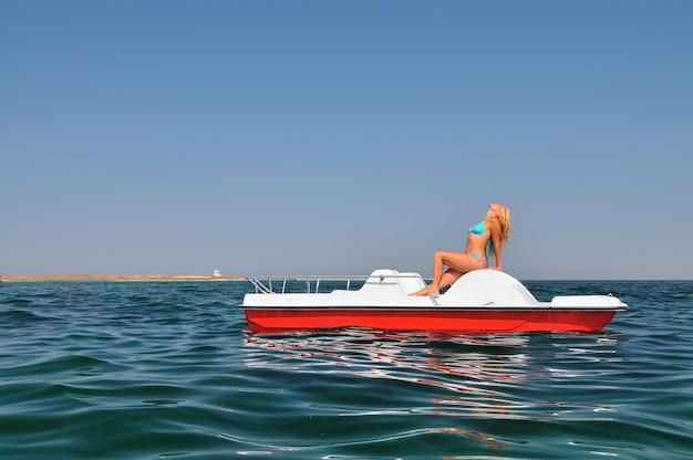 Jonge blonde vrouw in blauwe bikini zittend op een witte catamaran en genieten van zonneschijn op zonnige zomerdag. geluk, vakanties en vrijheid concept
