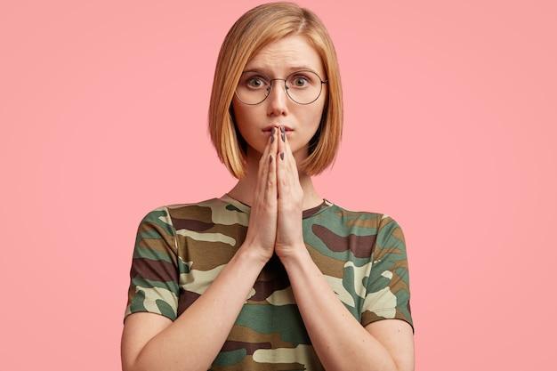 Jonge blonde vrouw in camouflaget-shirt