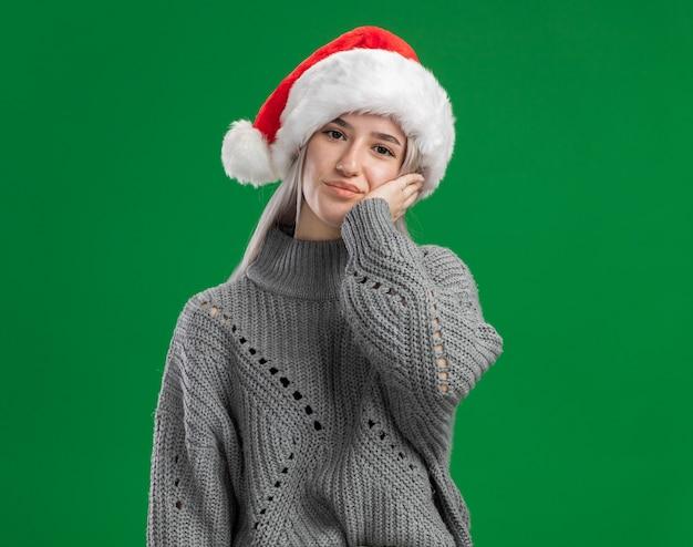 Jonge blonde vrouw in de winter sweater en kerstmuts kijken camera met hand op haar wang blij en positief staande over groene achtergrond