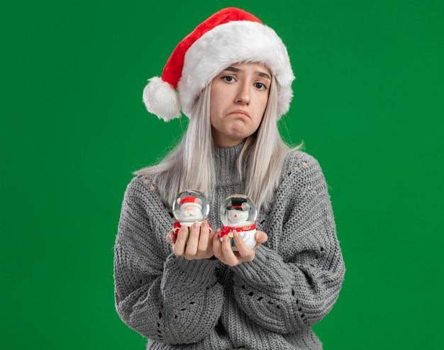Jonge blonde vrouw in de wintertrui en de kerstmuts die kerstmisstuk speelgoed sneeuwbollen houden die camera verward die geen antwoord hebben die zich over groene achtergrond bevinden