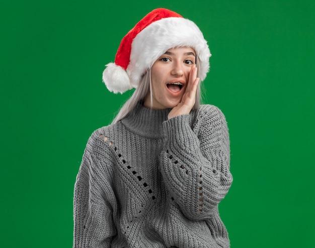 Jonge blonde vrouw in de wintertrui en kerstmuts die een geheim fluisteren met hand dichtbij mond die zich over groene achtergrond bevinden