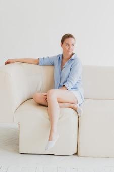 Jonge blonde vrouw in een blauw shirt zit op een bank in een lichte kamer