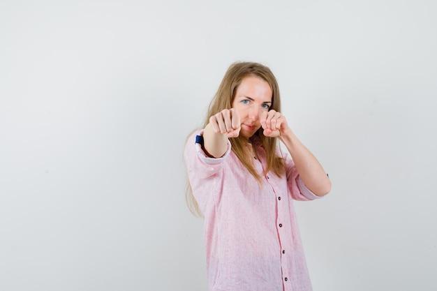 Jonge blonde vrouw in een casual roze shirt bereid om te vechten
