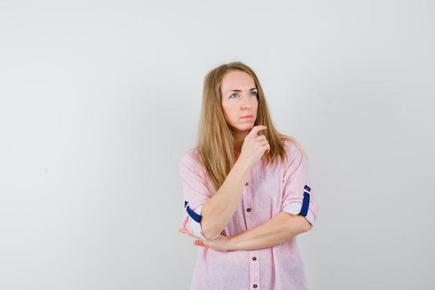 Jonge blonde vrouw in een casual roze shirt