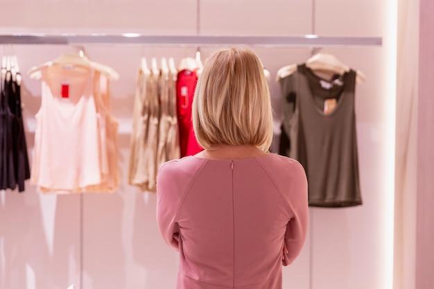 Jonge blonde vrouw in een kledingwinkel. achteraanzicht. moeilijke keuze.