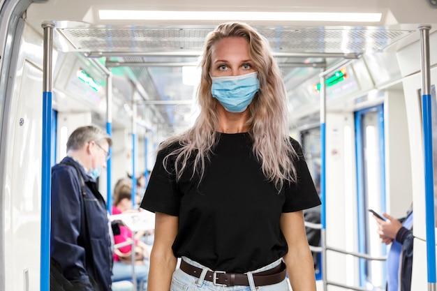 Jonge blonde vrouw in een masker in een metrowagen