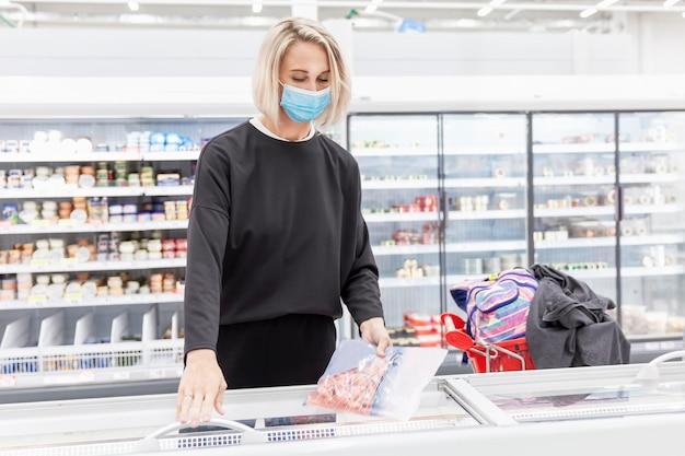 Jonge blonde vrouw in een masker in een supermarkt in de gekoelde voedselafdeling. coronapandemie.