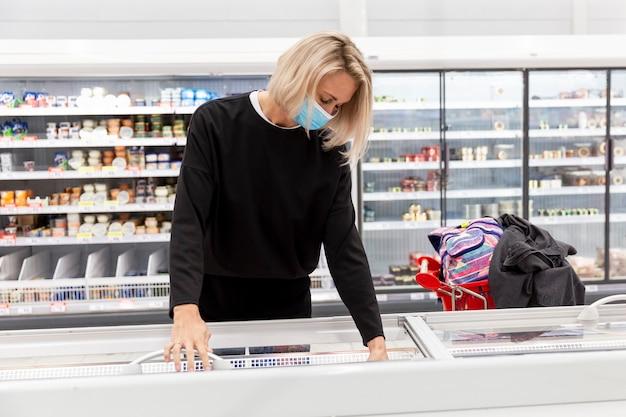 Jonge blonde vrouw in een medisch masker in de winkel op de afdeling met diepvriesproducten