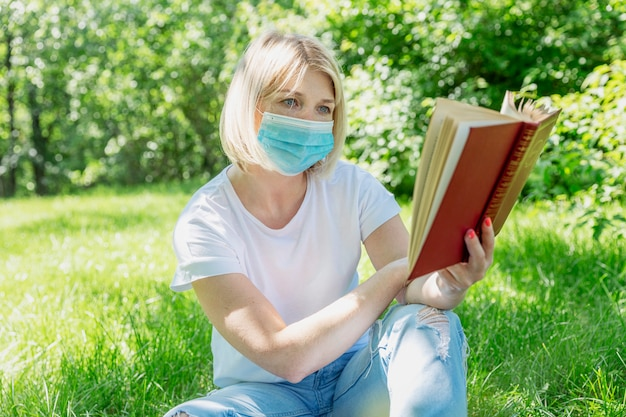 Jonge blonde vrouw in een medisch masker zit op het gras met een boek in het park. kamperen op een zonnige dag. voorzorgsmaatregelen tijdens de pandemie van het coronavirus.